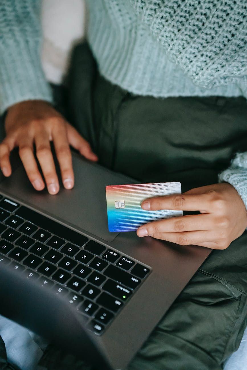 crop ethnic buyer with plastic card shopping online on laptop